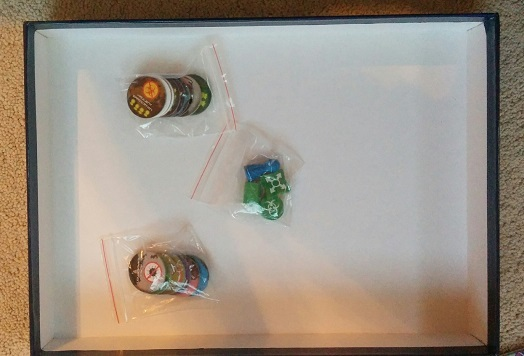 The leftover items: the lab tokens, a meeple, a research station and the epidemic / outbreak trackers, are placed in plastic bags and stored under the inserts.